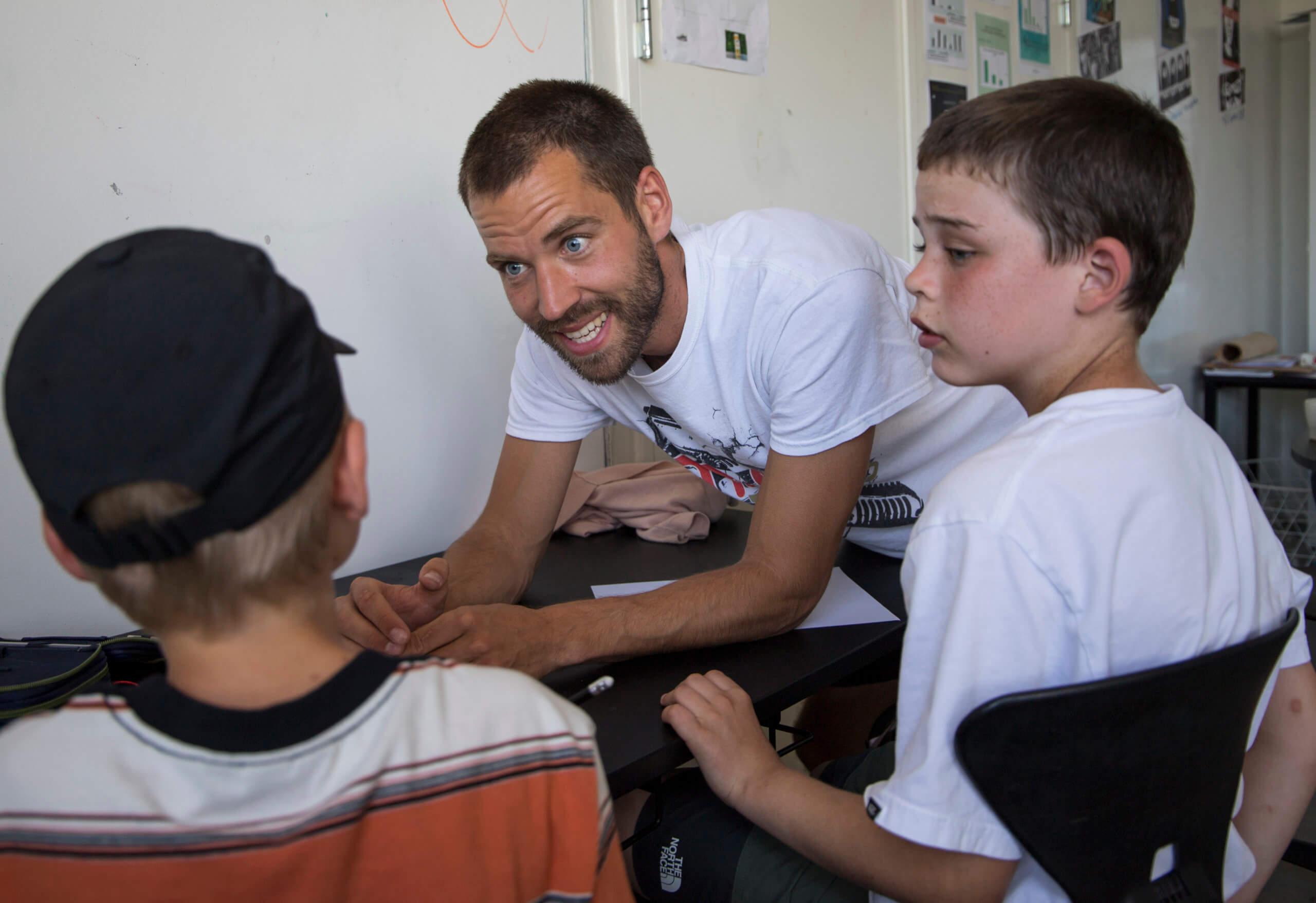 Lærer står ved bord og taler med to elever