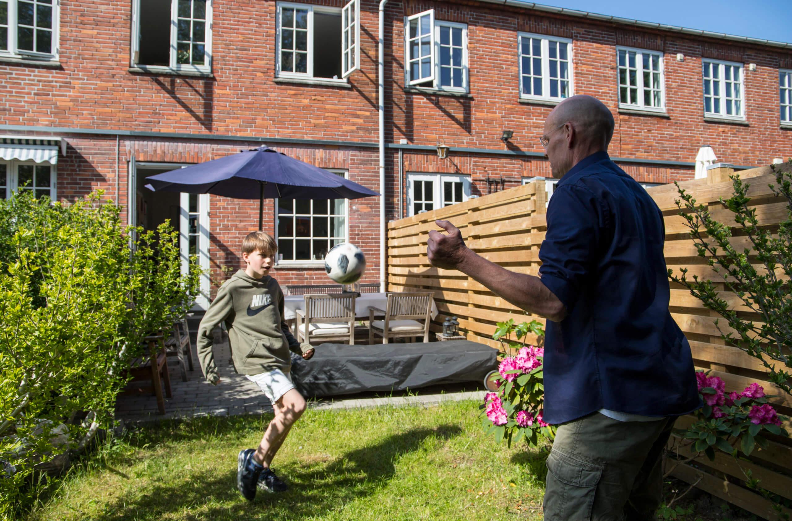 Søn og far spiller fodbold i haven