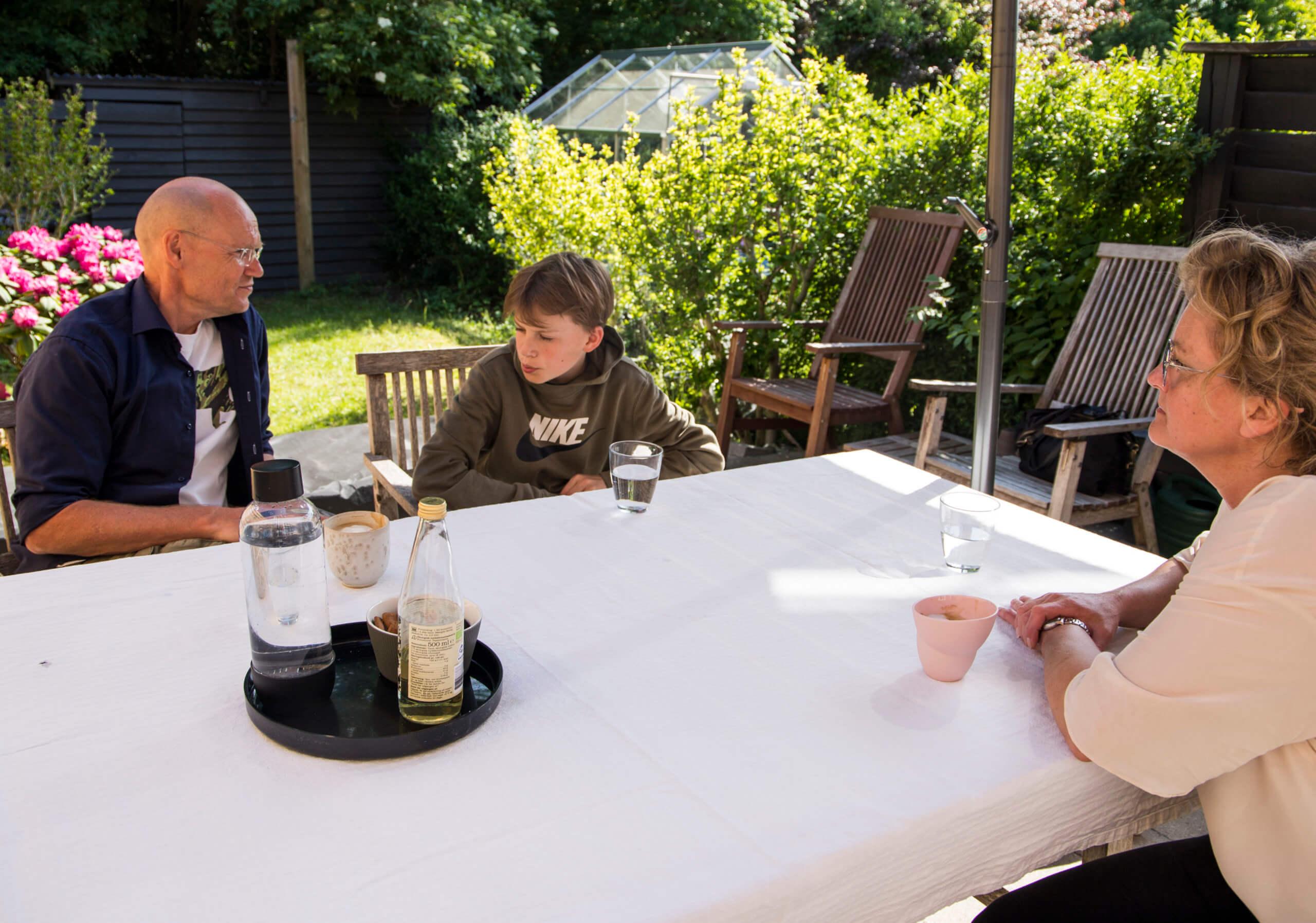 Far, søn og mor sidder ved havebordet